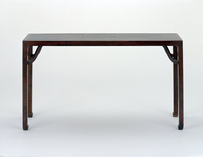 thin rectangular table; unadorned; feet emphasized; curved leg support reaches from under table top