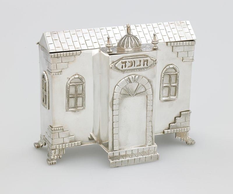 building with arched doorway in a protruding porch; 4 arched windows; roof flips up to reveal candle holders