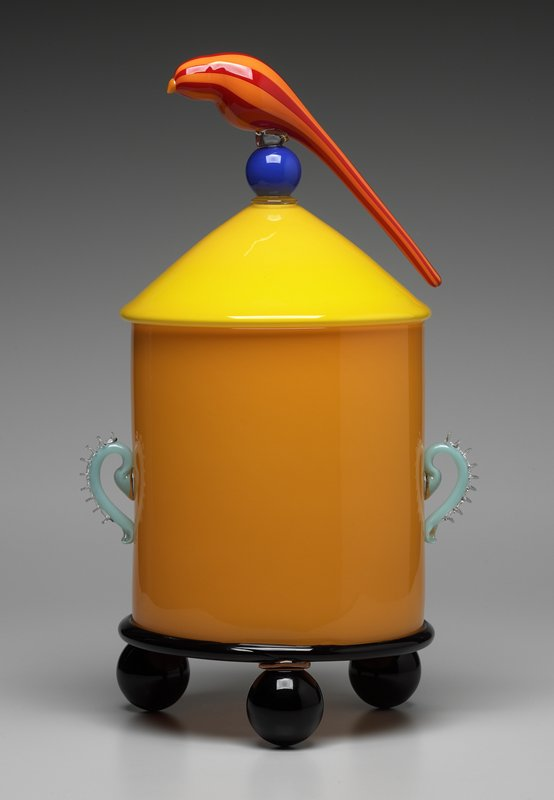 orange jar with 3 round black feet and 2 turquoise colored handles; yellow lid with orange and red bird sitting on round blue handle