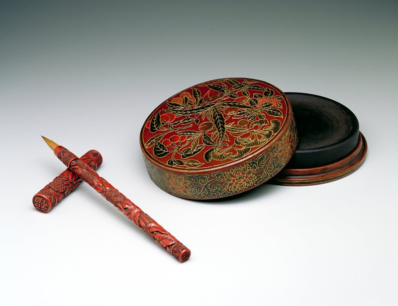 brush with carved cover and handle; circular medallions decorated with geometric patterning scattered over an organic leaf pattern background; meandering band at brush tip and lower end of cover