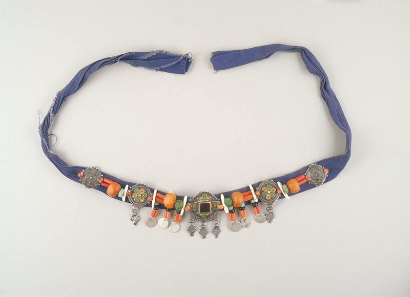 blue cloth headband with applied decoration; five metallic medallions alternating with amber beads in varying colors and sizes; central medallion has square red stud, central three enameled; groups of coins and diamond shapes hang from bottom edge at center