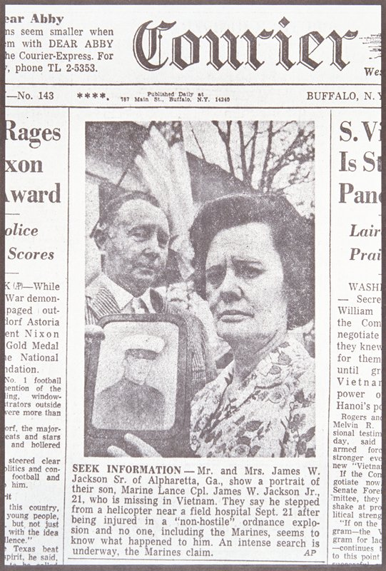 newspaper photograph of a man and woman; the woman is holding a framed photograph of a marine in uniform