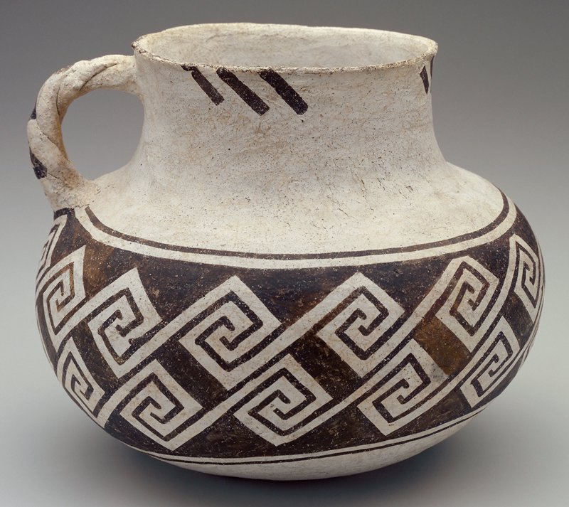 White with dark brown/black geometric pattern on central band; brown lines beneath lip and on handle.
