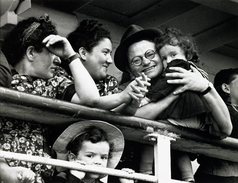 black and white photograph of two women, man wearing glasses holding a child and young boy leaning against railing