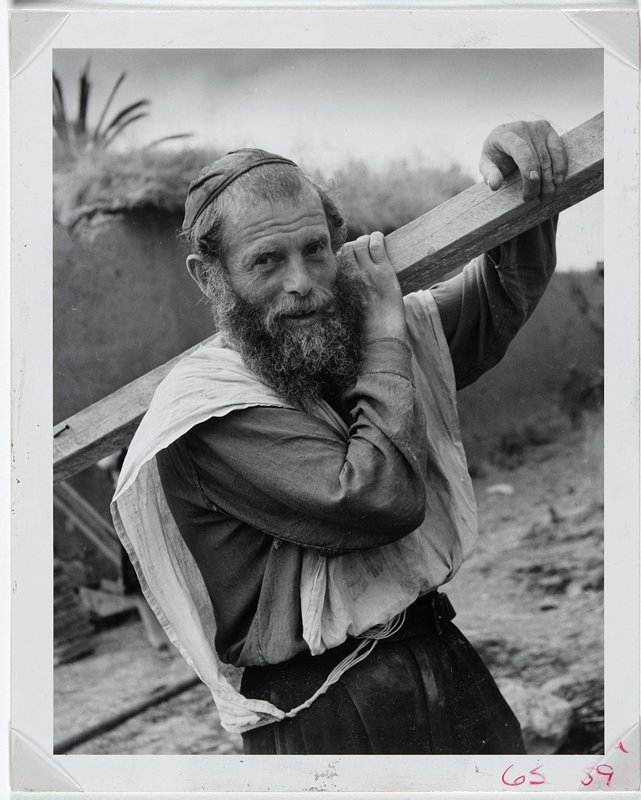 bearded man looking into camera carrying a piece of lumber over his shoulder