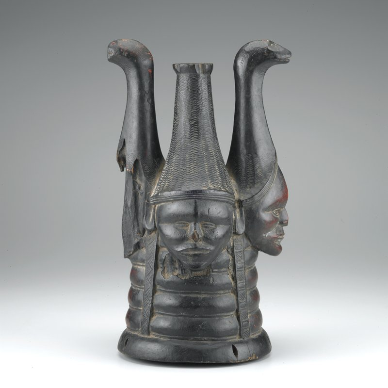 hatlike mask with 4 faces, 2 wearing headdresses with animal heads on long necks; 1 face totally lost due to insect damage