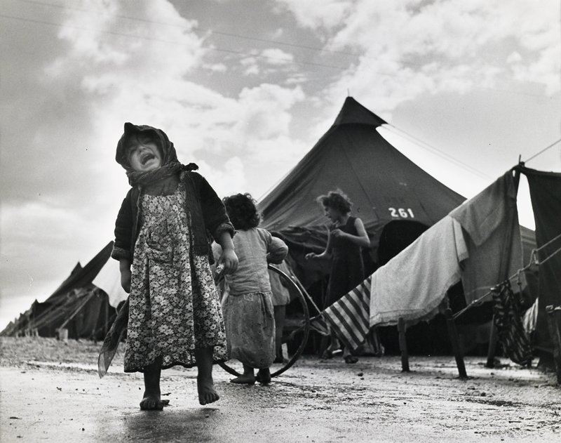 black and white photograph of little girl crying in front of tent #261 October/November 1950