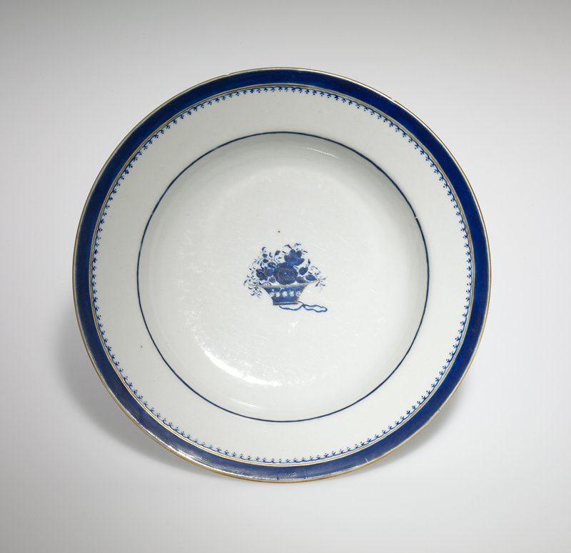 blue and white; small container of flowers with a ribbon underneath at center; gilt details at rim and center