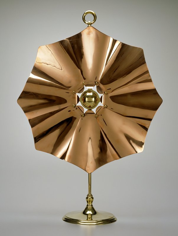 firescreen with floral design; copper 'petals' project outward from domed brass center; brass stand