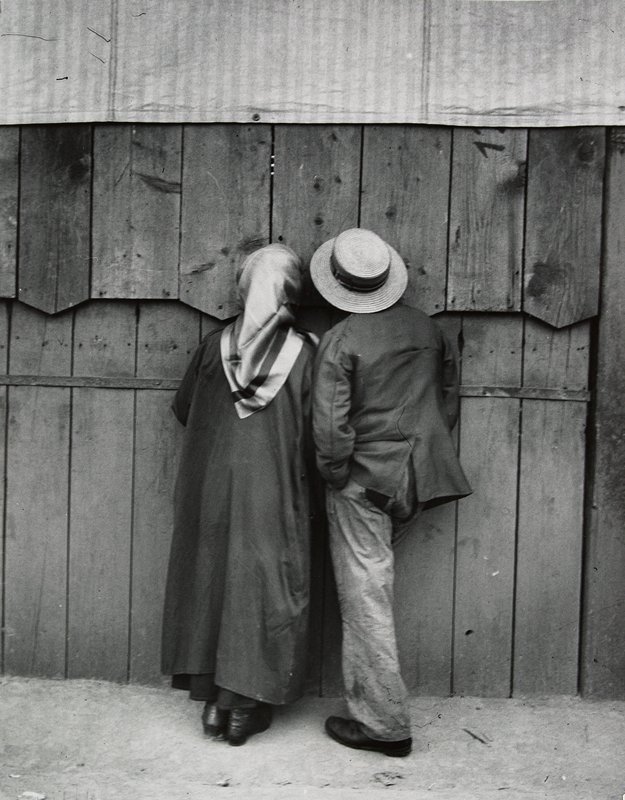 two people looking through cracks in a wooden fence