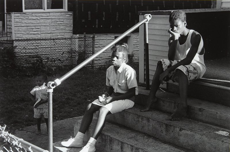 black and white photo of three young girls, two seated on steps