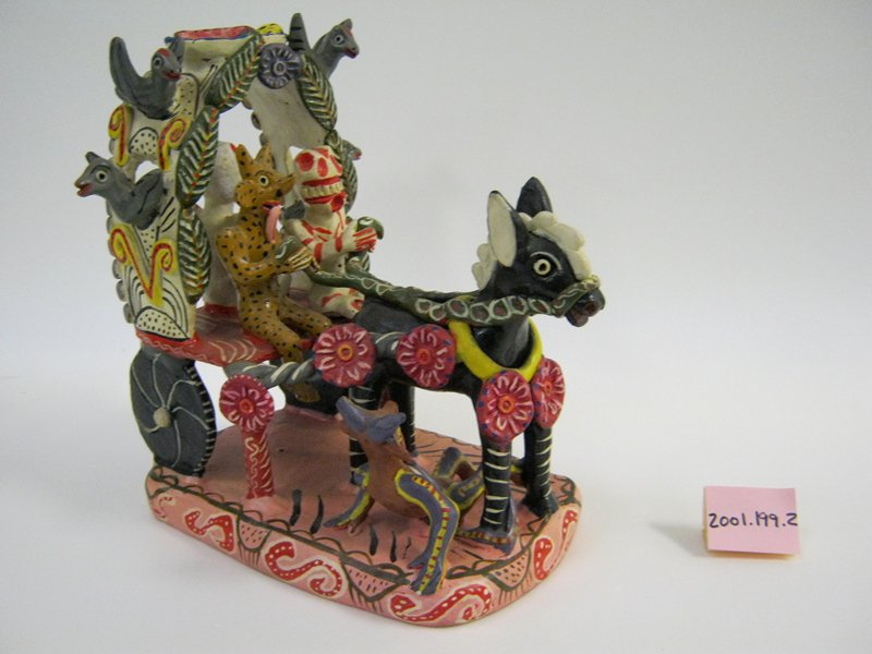 black donkey pulling a wagon with a skeleton and a demon in front and a demon with a ball in back; demon lying under donkey; 4 birds and a bowl of fruit on wagon cover; pink base