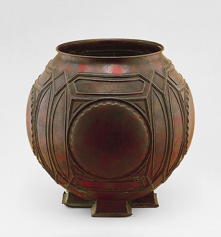 molded and hand-hammered; of spherical form, worked in répeussé with four circular designs with crenelated edge, within elliptical and lozenge frame borders, raised on four spreading rectangular feet