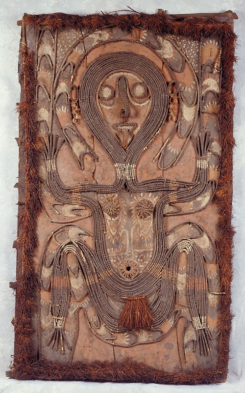 three sheets of bark joined and attached to a wood frame construction on back; seated female figure depicted, body bordered by a banded line; fringe border around exterior of panel; hands up at sides; five hoops hanging from each ear; tongue stuck out