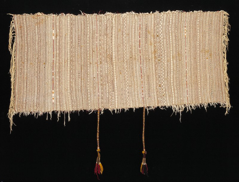 two tassels top center (26 inches); fringe, left and right side; loose threads on back, visible top and bottom; vertical bands of decoration (white, brown, black, gold and dark red). Woven fabric.