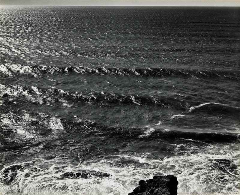 3 gently breaking waves with rock at center bottom; horizon very high in picture plane