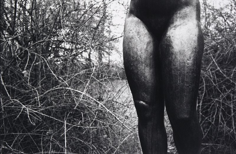 black and white photo of bottom half of female nude sculpture
