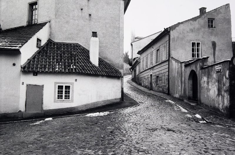 black and white photo of cobblestone street; house with tile roof on left