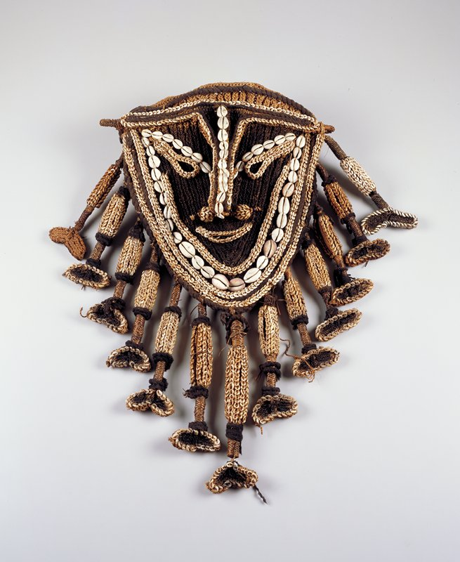 shield-shaped face with raised features delineated with 3 different sized cowrie shells; decorated wood stick through nose; 13 radiating hanging pendants with shells and ending in bean-shaped elements
