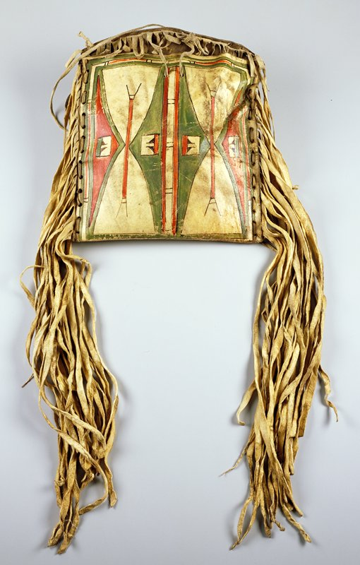 Bag with short flap at top; long fringe along sides, short fringe on top flap; geometric decoration with triangles and lines on front and large X with 4 stars on back in red, green and black