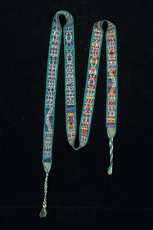 long woven band, green stripes on sides, central band of geometric motifs green, orange, blue, magenta, pink; several sections of inscriptions