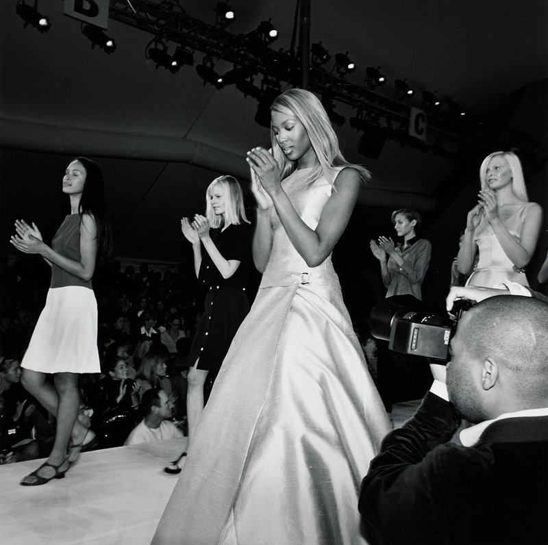 5 models at a fashion show walking in 2 rows down a runway, clapping; photographer in LRC
