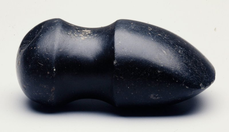 Black stone with one pointed short end; incised area around side near top