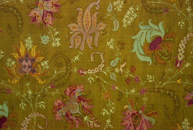 shawl, doshalla (long shawl) finely woven of olive green with design of rambling floral sprays and leaves in green, rose, yellow, orange, blue outlined in embroidery stitch; two borders on ends, the wide outer one composed of vari-colored stripes alternating with olive green, all with Mihrab tops enclosing single flowering plants; lined at one end with strip of black cotton, and furnished at one end with brass rings for hanging, fringed ends, narrow border on sides