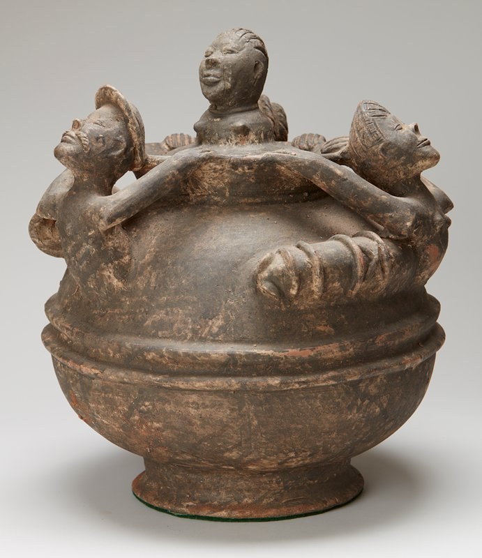 3 upper bodies of figures extending up from vessel shoulder, reaching backward to hold rim; bust of woman on cover; dark patina
