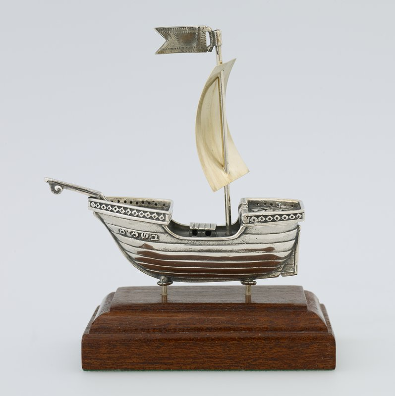 Spice box in the form of a silver sailboat with gold sail, surmounted by a flag; attached to a wood base