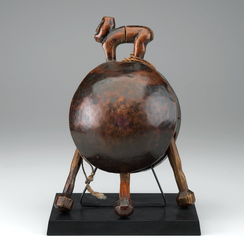 roughly spherical bell with 3 clappers topped by a carved quadruped standing with back legs and front legs carved as one, with human head; reddish mottled brown; glossy patina