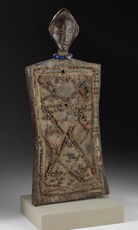 rectangular memory board lukasa topped by a head with a smooth peaked coiffure; necklace of blue glass beads; multicolored beads arranged in a lattice pattern on board; glossy patina on the head and back