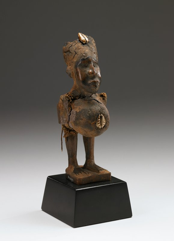 asexual figurine standing with legs apart on a rectangular base with compacted masses of symbolic ingredients inlaid with cowrie shells on the abdomen and head; tukula encrustations and area of glossy patina