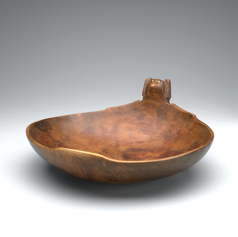"large bowl with rounded bottom; ""handle"" in the shape of a stylized animal head, with brass tack eyes"