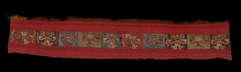 red at top and bottom with central band of repeated multicolored figures with large eyes, long toes and fingers and bared teeth; mounted between 2 pieces of plexi