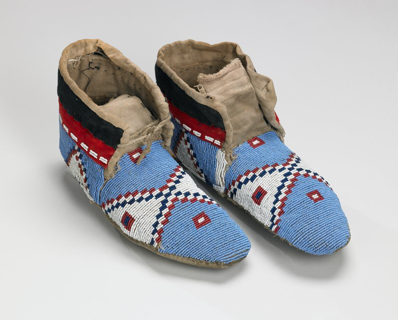 hide soles; canvas uppers; black and red cloth collars around ankles; geometric designs of red, white and dark blue on light blue ground