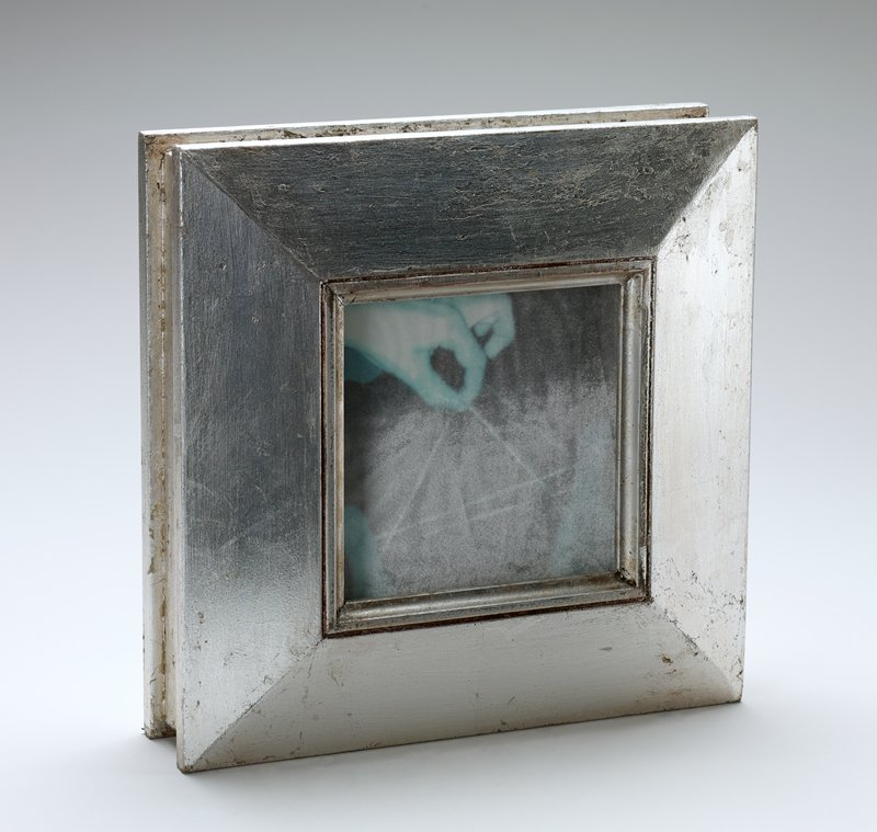 narrow box, silver leafed; window panel on each large side with aqua and grey images on velvet; slot on top; inscription on top