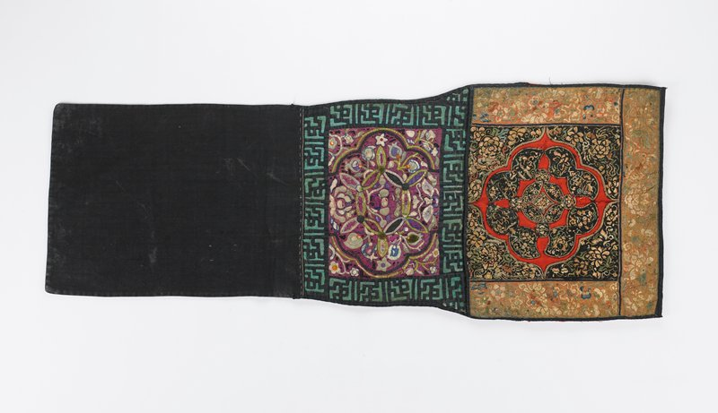 part of a baby carrier without ties; top square panel with black and red appliqués; black pieces are embroidered overall with tan, brown, white, cream, blue and green flowers; panel bordered on three sides with peachy tan embroidered floral bands accented with sequins; bottom rectangular panel has floral appliqués on purple ground; this panel bordered with black and green geometric appliqués; black and blue backing