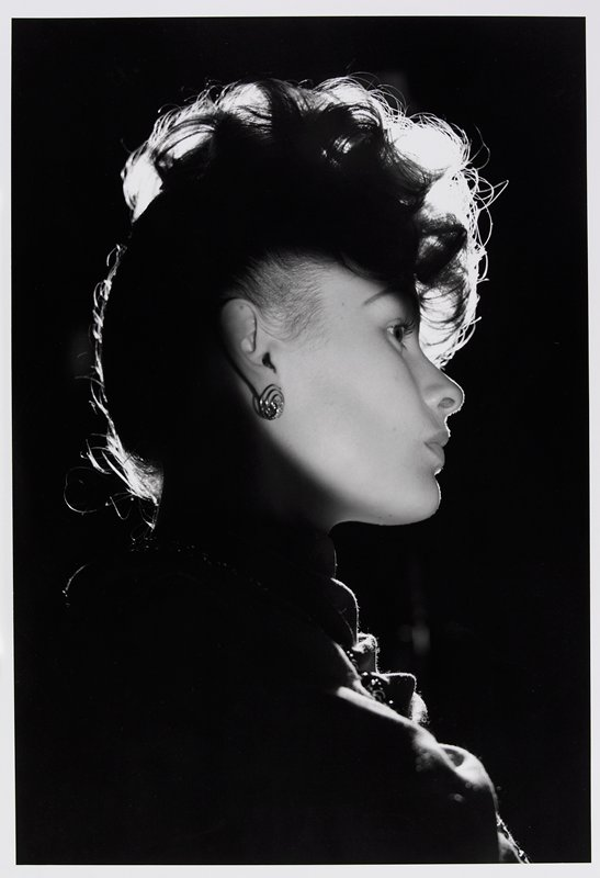 profile of a woman's head and shoulders; spotlight on woman's facial features and PR ear; woman has updone hair and wears spiraling earring