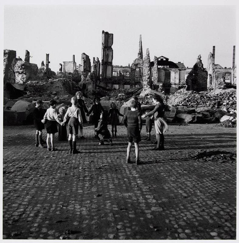 children playing ring-around-the-rosie in front of ruined buildings