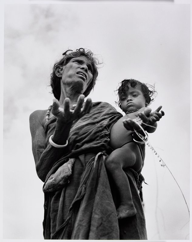 view upward of standing woman with unkempt hair, hands open and palms up, holding a toddler on her PL hip