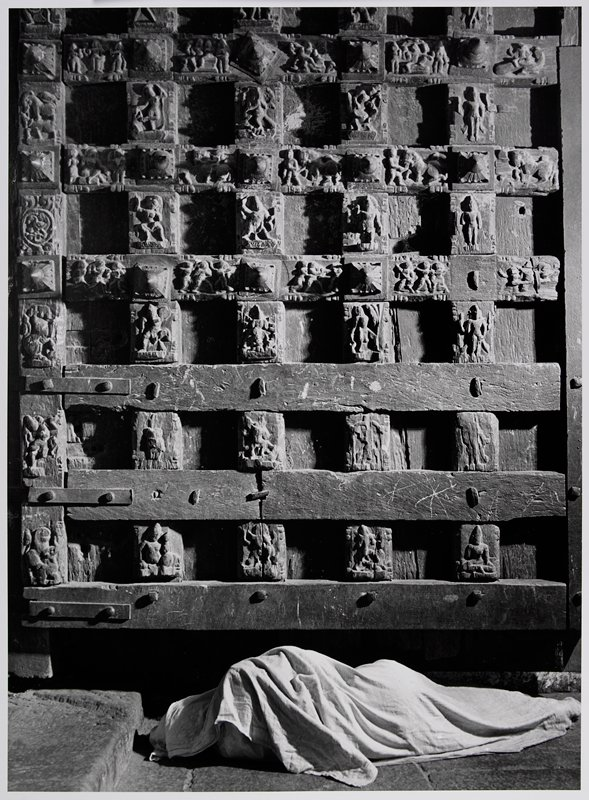figure completely covered in a cloth, lying on ground before a wooden door with carvings in a lattice design