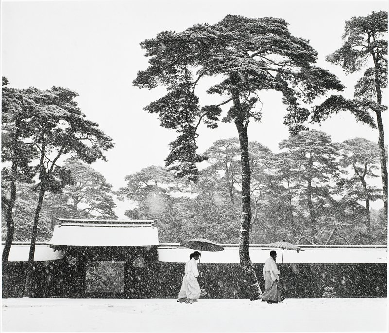2 pairs of figures in kimonos walking in the snow under 2 umbrellas; roofed wall with open gateway behind figures; tall trees
