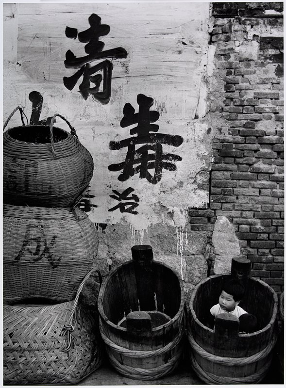 3 large stacked straw baskets at L; 2 large wooden barrels next to baskets; child hiding in barrel in LRC; whitewashed wall with large black characters behind baskets and barrels