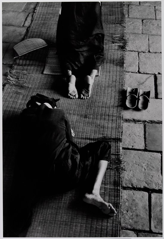 backs of 2 figures kneeling and bent over on a mat over stone blocks; pair of sandals at R