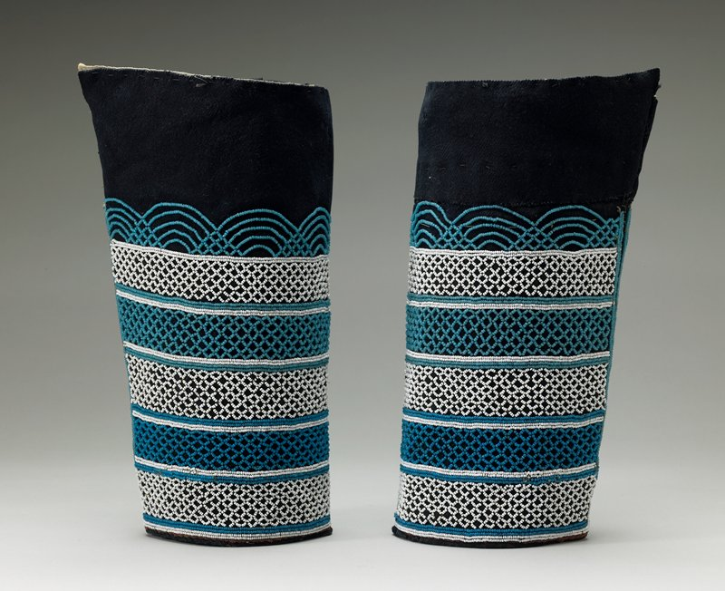 flaring tubular design; dark wool with beading overall in blues and white in openwork geometric design