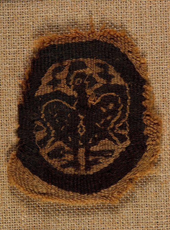 fragment of a medalion surrounding a bird in dark brown and tan