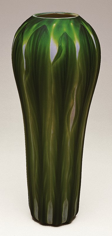 Hand-blown glass with wheel-carved cameo Favrille surface depicting attenuated leaves in deep green over a white glass ground; cylindrical form, swollen at the shoulder