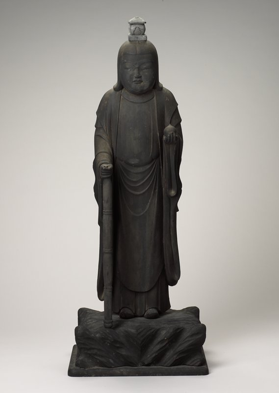 carved figure wearing a robe, holding a sphere with a pointed top in PL hand and a staff in PR hand (detachable); small house-like light grey wood attachment at top of head; figure is dark brown; 2 wooden stakes at bottom for attachment to base