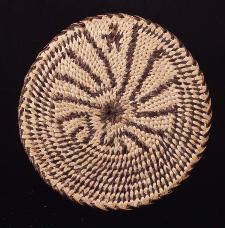 Miniature flat plaque; coiled. Design consists of a central devil's claw from which emanates a maze pattern, at the entrance of which stands a human figure. This pattern is called the House of Shuihii Ki, a legendary figure, who supposedly lives in the mountains where no one can find him. Colors are natural and black.